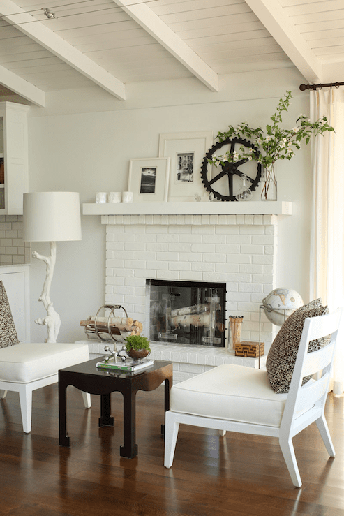 living rooms - white branch lamp white painted brick fireplace white chairs brown pillows  Bear Hill Interiors.  white painted brick fireplace,