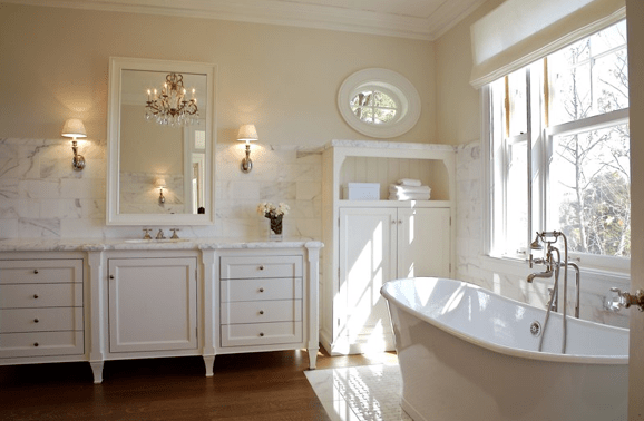 bathrooms - ivory walls . white bathroom vanity cabinets white beveled mirror calcutta marble tiles basksplash sconces vintage tub double sinks