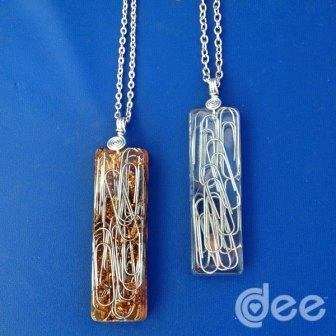 Pendentes com clips. O da esquerda tem verniz no meio da resina, que lhe dá o aspecto dourado