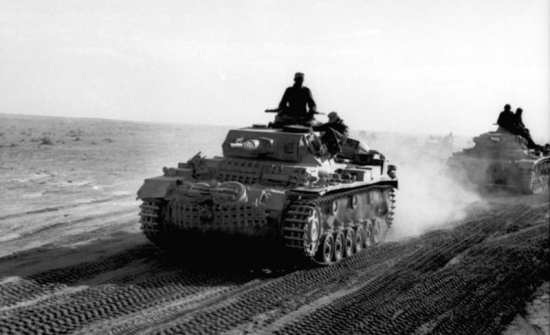 Afrika Korps Panzer III tanks drive through the desert. Field Marshall Erwin Rommel's Afrika Korps used these relatively light tanks with great success in North Africa. Bundesarchiv photo