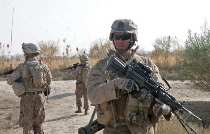 Lance Cpl. Garrett Gamble, a squad automatic weapon gunner with Golf Company, 2nd Battalion, 2nd Marine Regiment, turns to check the rear during a patrol through the fields and town of Loy Darwayshan, in Garmsir, Afghanistan, Dec. 4, 2009. The Marines patrolled with local Afghan Border Police and were able to find one improvised explosive device and two bags of IED-making materials. U.S. Marine Corps photo by Lance Cpl. Dwight A. Henderson