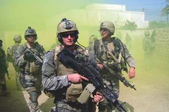 In an undated file photo provided by the U.S. Navy, Master-At-Arms 2nd Class (SEAL) Michael A. Monsoor participates in a patrol in support of Operation Iraqi Freedom. Monsoor was awarded the Medal of Honor posthumously for diving onto a grenade to save his teammates in Ar Ramadi, Iraq on Sept. 29, 2006. Monsoor also received the Silver Star for his actions in May during the same deployment in 2006 when he exposed himself to heavy enemy fire to rescue and treat an injured teammate. Photo courtesy Monsoor family.