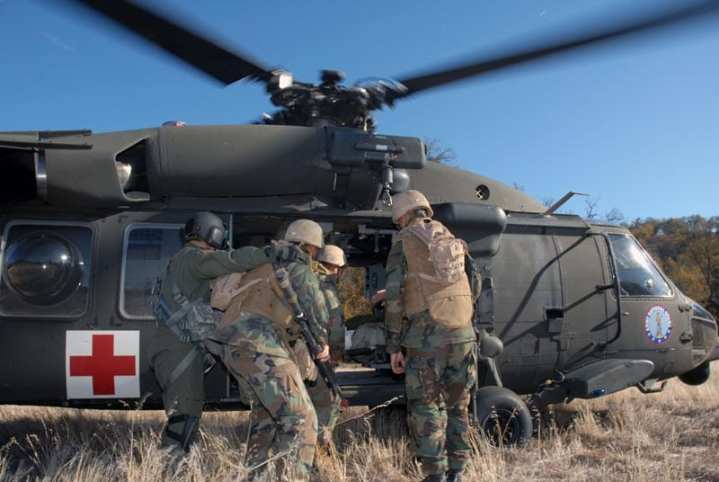Seabees from Naval Mobile Construction Battalion (NMCB) 17 load a patient into a UH-60Q Black Hawk medical evacuation helicopter during a mass casualty drill. The UH-60Q carries a FLIR Systems Star SAFIRE sensor turret at the nose. U.S. Navy photo by Mass Communication Specialist 2nd Class Kenneth W. Robinson.