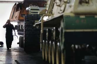 An Anniston Army Depot mechanic approaches an Army vehicle that has had the tracks removed and is being reset for service in Anniston, AL, on Sept. 18, 2008. Army photo by D. Myles Cullen (released)
