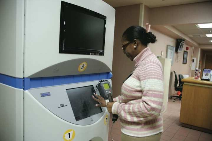 Nita Hargrove enters her daughter's information into the Automated Prescription Machine (APM) at Reynolds Army Community Hospital. The APM is available 24 hours a day to pick up refills. Pharmacy automation is reducing costs while increasing efficiency and patient safety. Photo courtesy of Courtney Griggs, Fort Sill Cannoneer.