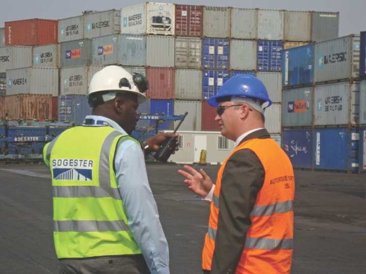 Lt. Daron Tanko (right), Coast Guard International Port Security Liaison Officer, discusses cargo security with the Port Facility Security Officer in Luanda, Angola, in 2010. For countries that conduct maritime trade with the United States, the Coast Guard meets with the people who are responsible for port security and verifies that their ports comply with international security regulations. U.S. Coast Guard photo