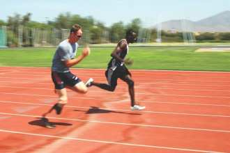 U.S. Navy Cryptologic Technician 1st Class Casey Tibbs runs with a teammate on the track at the ARCO Olympic Training Center in San Diego, Calif., July 15, 2008, to prepare himself for his Paralympics events at the Beijing Olympics. Tibbs represented the United States in several events, including shotput, discus, and long jump during the 2008 Olympic games. U.S. Navy photo by Mass Communication Specialist 3rd Class David A. Brandenburg.