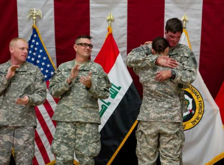 Capt. Sam Brown hugs his wife, Capt. Amy Brown, after arriving in Baghdad Dec. 28, 2009, to take part in Operation Proper Exit. Sam Brown suffered full-thickness burns to 30 percent of his body in Kandahar, Afghanistan, but has returned to Iraq to tell his story to service members and help find closure. Lee Craker, Multi-National Corps-Iraq Public Affairs Office photo