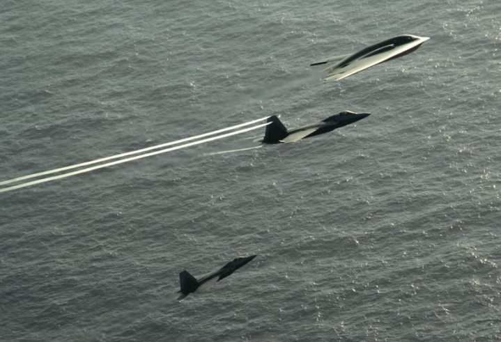 F-22 Raptors and a B-2 Spirit
