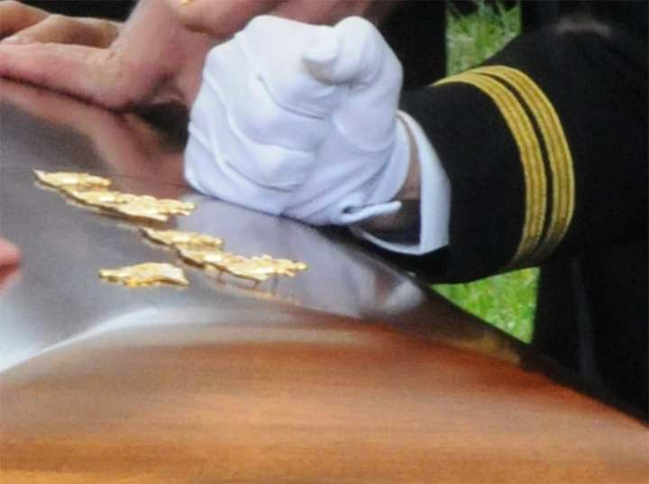 SEALS pound their insignia into the coffin of a fallen brother SEAL during a funeral
