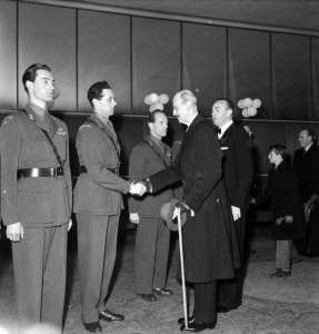 King Haakon VII of Norway at the premiere of the film Kampen om tungtvannet (Operation Swallow: The Battle for Heavy Water), Oslo, Norway, Feb. 5, 1948. Soldiers in uniform, from the left: Joachim Rønneberg, Jens Anton Poulsson shaking hands with the king, Kasper Idland. Oslo Museum photo by Leif Ørnelund