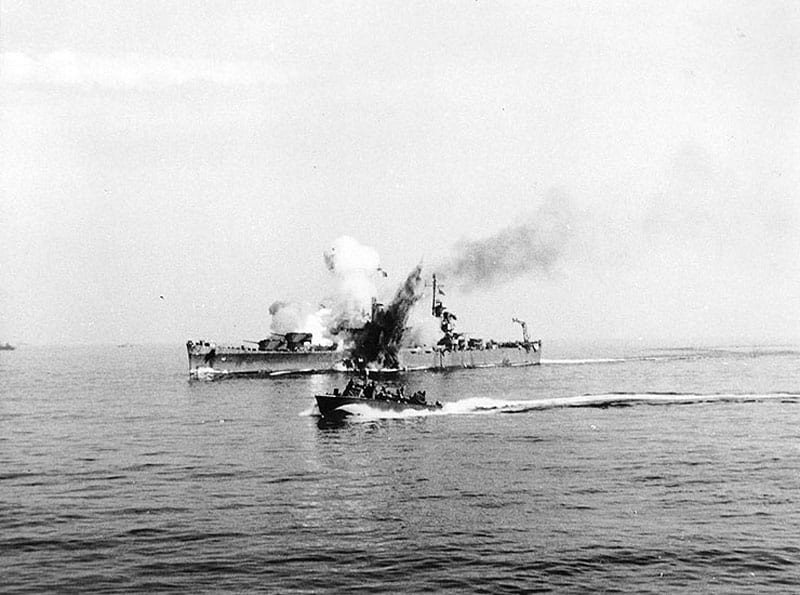 The USS Savannah (CL 42) is hit by a German radio-controlled bomb, while supporting Allied forces ashore during the Salerno operation, Sept. 11, 1943. The bomb hit the top of the ship's number three gun turret and penetrated deep into her hull before exploding. This photograph shows the explosion venting through the top of the turret and also through Savannah's hull below the waterline. A PT boat is passing by in the foreground. U.S. Naval Historical Center photo
