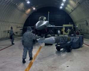 Senior Airman Kristopher Steele, Staff Sgt. Chad Smith and Airman 1st Class Kadeem Wright prepare to load a bomb onto an F-16 Fighting Falcon at Kunsan Air Base, Republic of Korea, Jan. 14, 2013. This was part of Beverly Midnight 13-1, an exercise which tests airmen's ability to respond to various scenarios such as mortar attacks and injured personnel. All three are members of the 8th Aircraft Maintenance Squadron. U.S. Air Force photo by Staff Sgt. Jonathan Fowler
