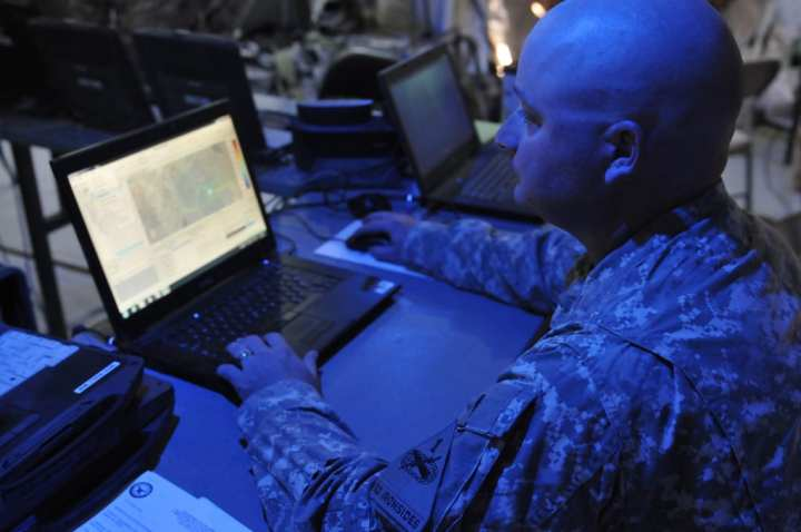 Staff Sgt. Michael Mitchell, an electromagnetic spectrum manager for 2nd Brigade Combat Team, uses a Joint Spectrum Management Planning Tool to track mission progress in the field from inside the Headquarters Tactical Operations Center as part of Network Integration Evaluation 14.2 at Fort Bliss, Texas, May 1, 2014. The network has the potential to connect forces at all echelons and empower leaders with the right information at the right time, but the test also allows units to train in collective tasks and exercise mission-command principles. U.S. Army photo by Staff Sgt. Richard Andrade; 16th Mobile Public Affairs Detachment