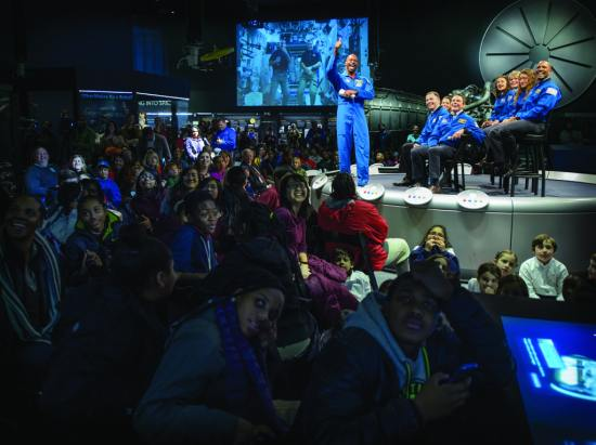 NASA associate administrator for education and former astronaut Leland Melvin gives a thumbs up to International Space Station (ISS) crew members Rick Mastracchio, screen left, and Michael Hopkins during a live downlink at an event where they and eight astronaut candidates talked with Washington, D.C.-area students and the public about the value of education in science, technology, engineering, and mathematics (STEM), Jan. 30, 2014, at the Smithsonian's National Air and Space Museum. NASA/Bill Ingalls