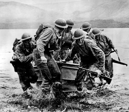 """Rangers come ashore from a small boat during amphibious training. They wear the old World War I-era """"Brodie"""" helmets but are armed with M1 Garands."""