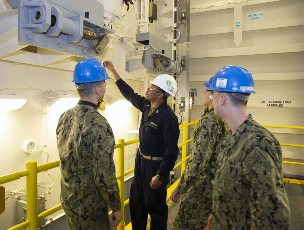Chief Machinist's Mate Franklin Pollydore, second from left, from Georgetown, Guyana, goes over safety procedures for the Upper Stage 1 advanced weapons elevator with Sailors from USS Gerald R. Ford's (CVN 78) weapons department. The elevator is the first to be delivered to the ship and marks a major milestone for Ford and the entire Ford-class of aircraft carriers. Ford is currently undergoing its post-shakedown availability at Huntington Ingalls Industries-Newport News Shipbuilding. (U.S. Navy photo by Mass Communication Specialist 1st Class Jeff Troutman/Released)