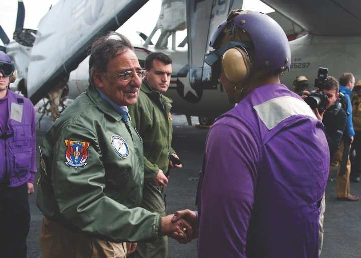 Secretary of Defense Leon Panetta, center, exchanges greetings with a U.S. sailor upon his arrival aboard the aircraft carrier USS Enterprise (CVN 65) in the Atlantic Ocean, Jan. 21, 2012. Enterprise was underway conducting a composite training unit exercise in preparation for its 22nd and final deployment. DoD photo by Mass Communication Specialist 3rd Class Scott Pittman, U.S. Navy
