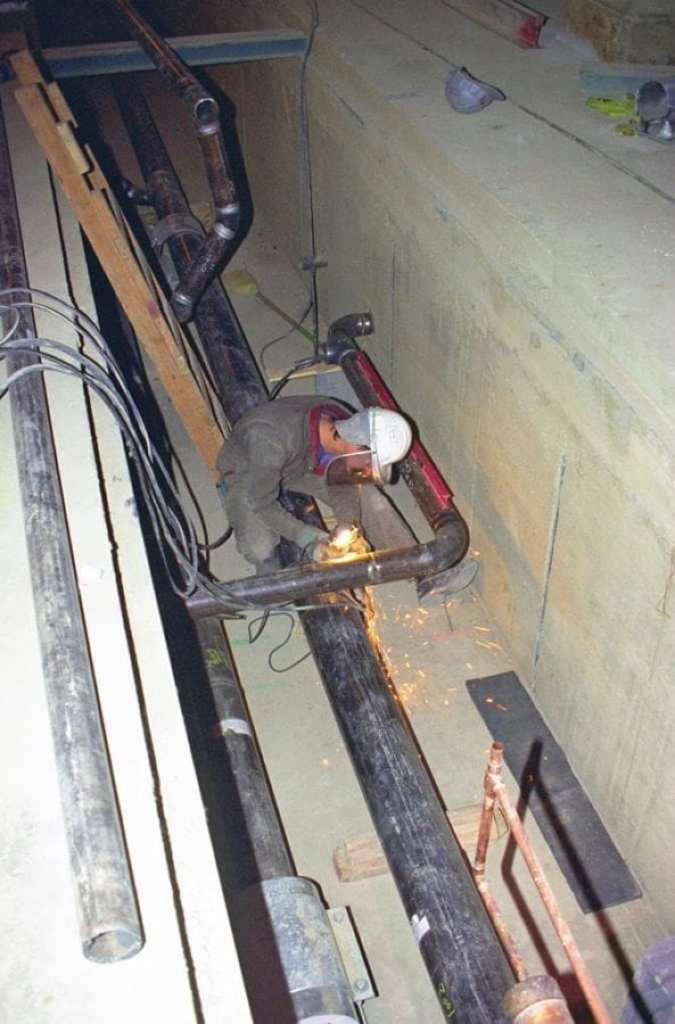 A welder works to install new piping during renovation. National Archives via Picryl