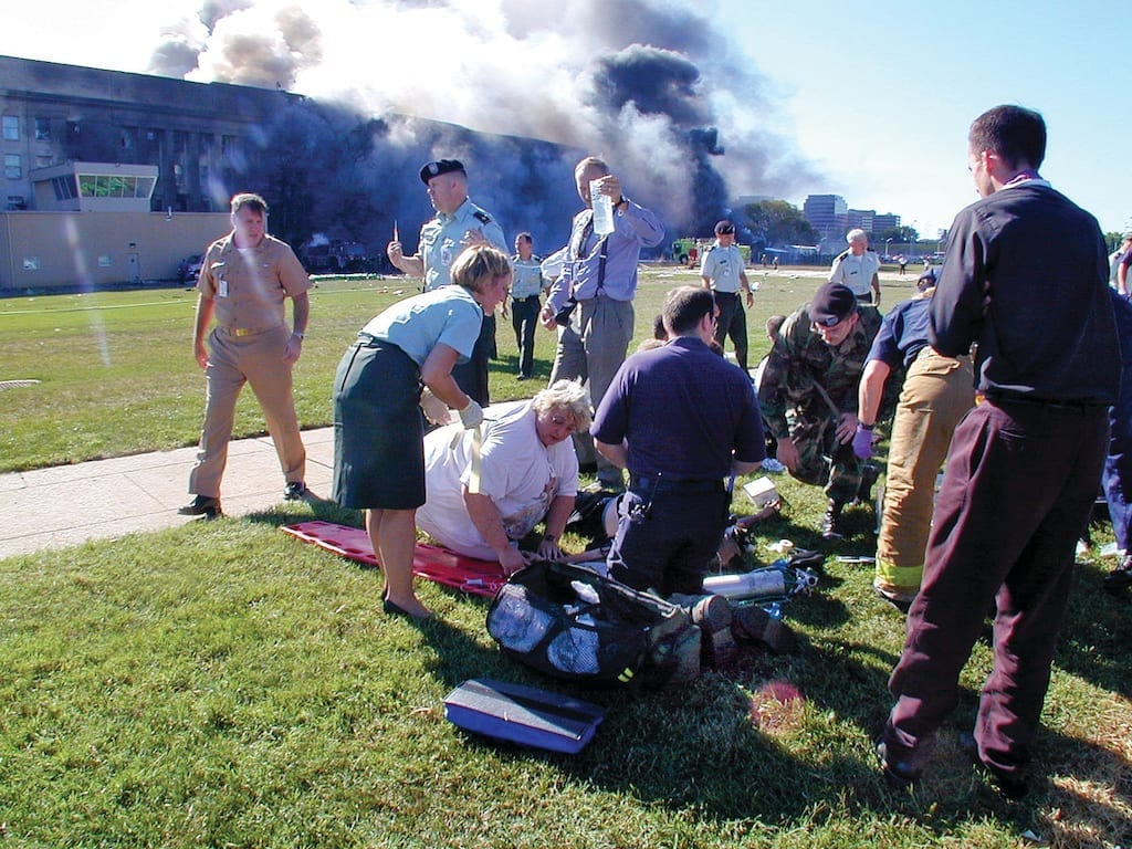 Medical personnel and volunteers work the first medical triage area set up outside the Pentagon after a hijacked commercial airliner crashed into the southwest corner of the building. U.S. Navy Photo by Journalist 1st Class Mark D. Faram
