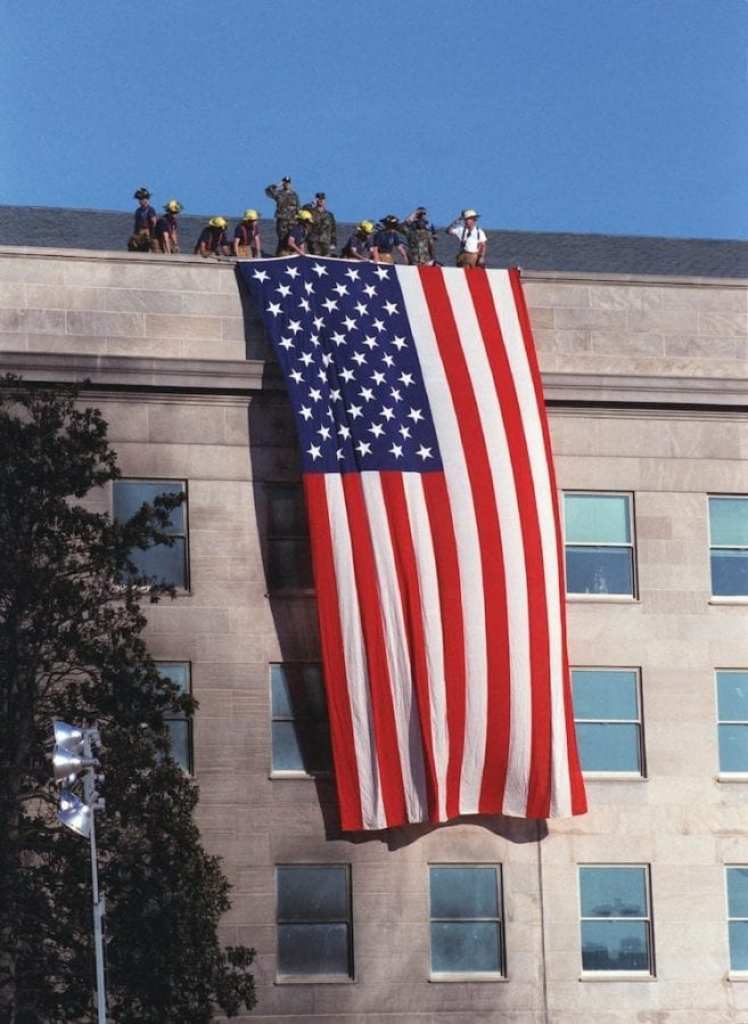 """Fire fighters and military personnel on the roof of the Pentagon unfurl a large American Flag during the Sept. 12, 2001, visit of President George W. Bush to the site of the previous day's terrorist attack on the Pentagon. As the flag was draped over the wall, just south of the site where American Airlines Flight 77 impacted the building, the disaster workers gathered around the president began to sing """"God Bless America."""" DoD photo by R. D. Ward"""