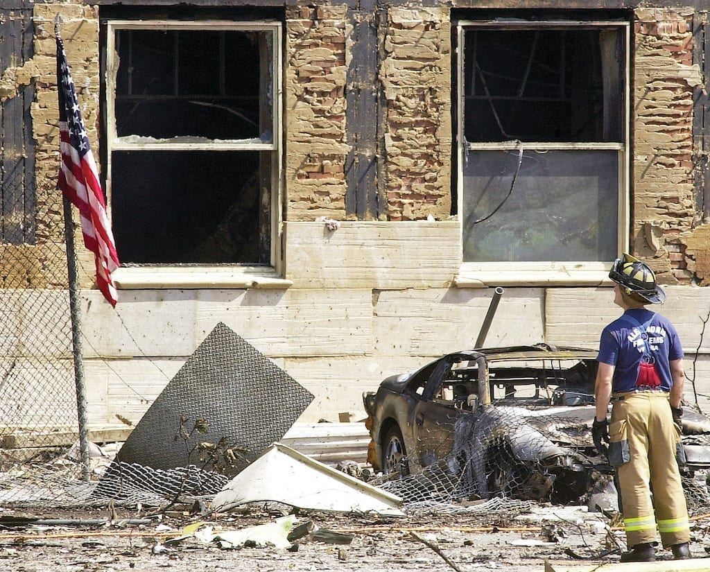 Standing before a burned-out hulk of an automobile, an Alexandria, Virginia, fireman inspects the damage to the Pentagon after a hijacked Boeing 757, American Airlines Flight 77, was deliberately crashed into the building on Sept. 11, 2001. The Pentagon attack followed an attack on the twin towers of the New York World Trade Center, where two fully loaded passenger airliners were flown into the buildings in what has been called the worst terrorist attack in history. U.S. Navy Photo by Journalist 1st Class Mark D. Faram