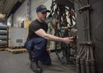 Mass Communication Specialist 2nd Class Anthony Flynn, assigned to the aircraft carrier USS Harry S. Truman (CVN 75), demonstrates the operational de-blousing capability of the flame-resistant, two-piece organizational clothing prototype. U.S. Fleet Forces Command will conduct a second wear test of the prototype later this year. The goal of the initiative is to provide a no-cost, safe, and comfortable organizational clothing option to the improved, flame-resistant variant (IFRV) coverall. (U.S. Navy photo by Mass Communication Specialist 2nd Class Stacy M. Atkins Ricks/Released)