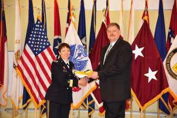Maj. Gen. Barbara R. Holcomb, commander of the U.S. Army Medical Research and Materiel Command and Fort Detrick, presented Dr. George Ludwig with his Senior Executive Service Flag during his SES induction ceremony, Feb. 21, 2017