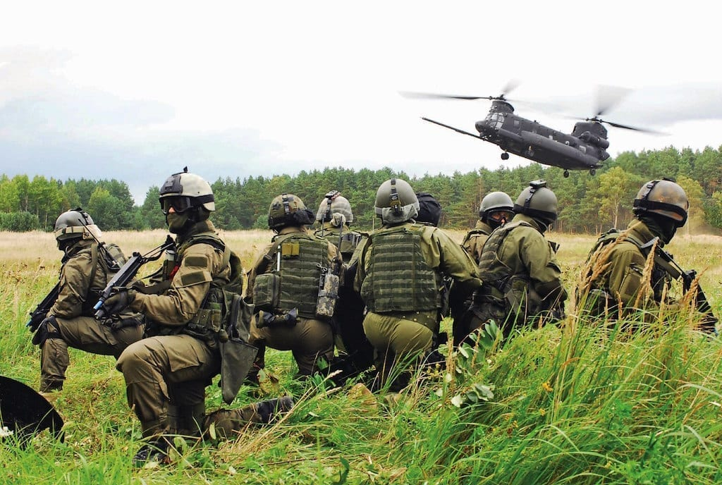 Coalition special forces wait for the MH-47G Chinook to land so they can extract their high value target during the opening ceremony for Jackal Stone 10 Exercise at Darwsko, Poland 20 Sept. Jackal Stone 10, hosted by Poland and Lithuania this year, is an annual international special operations forces (SOF) exercise held in Europe