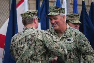 Rear Adm. Collin P. Green shakes the hand of Rear Adm. Tim Szymanski after relieving him as commander, Naval Special Warfare Command during a change-of-command ceremony at Naval Amphibious Base Coronado
