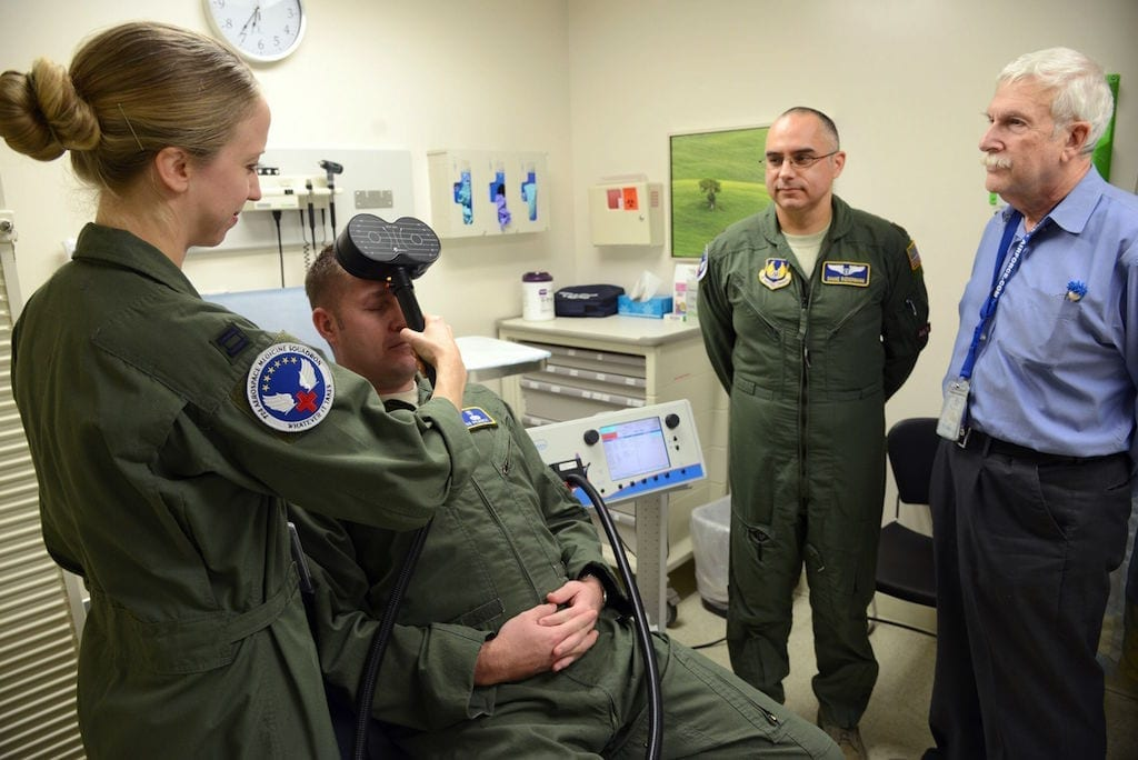 Dr. Stacy Zimmerman, an associate investigator, demonstrates using the transcranial magnetic stimulation on Capt. Josh Pearcy, a physician assistant, while Dr. Shane Biedermann and Dr. Harold Ginzburg observe. Biedermann, as the primary investigator, and his team, are looking for combat veteran volunteers with post-traumatic stress disorder to participate in this noninvasive study using electroencephalography