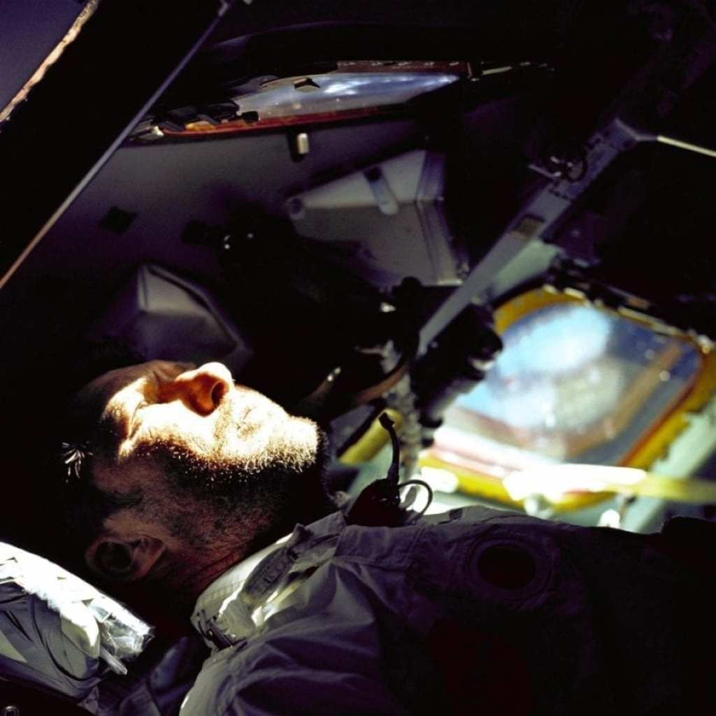 """A heavy beard covers the face of astronaut Walter M. """"Wally"""" Schirra Jr., Apollo 7 commander, as he looks out the rendezvous window in front of the commander's station on the ninth day of the Apollo 7 mission."""