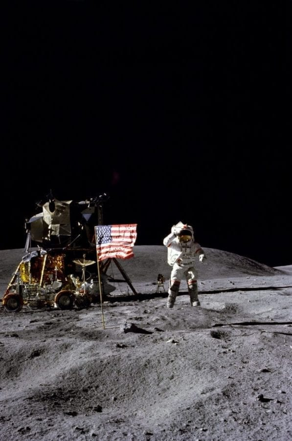 """Astronaut John W. Young, commander of the Apollo 16 lunar landing mission, jumps up from the lunar surface as he salutes the U.S. Flag at the Descartes landing site during the first Apollo 16 extravehicular activity (EVA-1). Astronaut Charles M. Duke Jr., lunar module pilot, took this picture. The Lunar Module (LM) """"Orion"""" is on the left. The Lunar Roving Vehicle is parked beside the LM. The object behind Young in the shade of the LM is the Far Ultraviolet Camera/Spectrograph. Stone Mountain dominates the background in this lunar scene."""