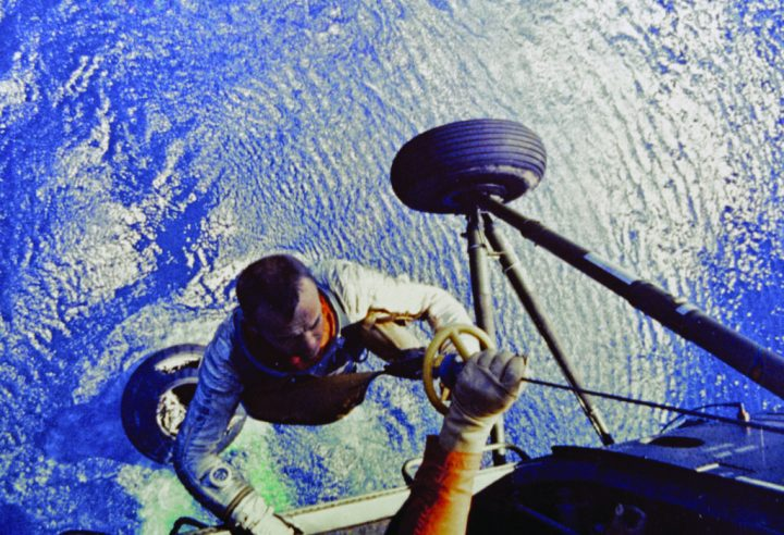 Shepard is hoisted aboard a U.S. Marine helicopter after splashdown of his Freedom 7 Mercury space capsule seen below his right arm.
