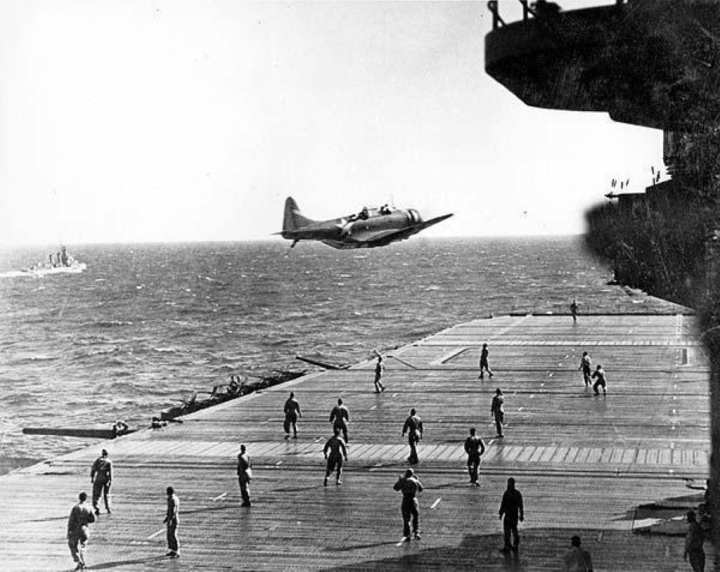 """A U.S. Navy Douglas SBD Dauntless drops a message container known as a """"bean-bag"""" on the flight deck of USS Enterprise (CV 6) while crewmembers dart to catch the message to deliver it up to the ship's bridge. (Photo provided by the Naval Aviation Museum)"""