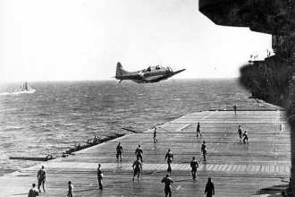 "A U.S. Navy Douglas SBD Dauntless drops a message container known as a ""bean-bag"" on the flight deck of USS Enterprise (CV 6) while crewmembers dart to catch the message to deliver it up to the ship's bridge. (Photo provided by the Naval Aviation Museum)"
