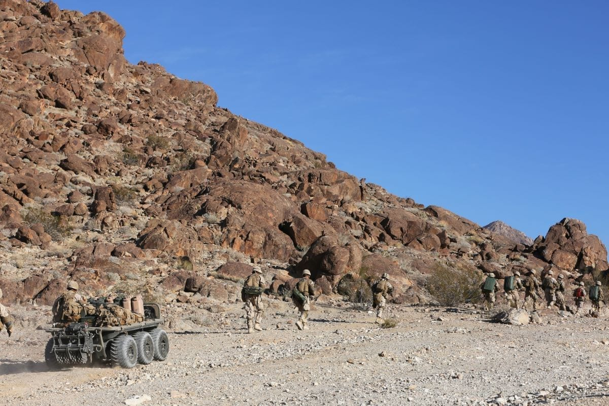 Marines and sailors assigned to Lima Company, 3rd Battalion, 5th Marine Regiment move toward their objective with a Logistics Multipurpose Unmanned Tactical Transport (Log-MUTT) carrying a portion of their gear during their Integrated Training Exercise at the Marine Corps Air-Ground Combat Center, Twentynine Palms, California, in November 2016, a training event within their predeployment training curriculum. The Marine Corps Warfighting Laboratory provided some different unmanned aircraft systems (UAS) and unmanned ground systems (UGS) for the Marines to employ during their training cycle.