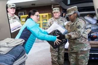 Capt. Kory Garbelman, U.S. Army Human Resources Command (left); Lauren Sneed, Rex Robley VA Medical Center, voluntary service assistant; Master Sgt. Neil Van Cura, HRC and Brig. Gen. Twanda (Tia) Young, HRC deputy commanding general, unload a van full of household goods HRC Soldiers and staff donated to the VAMC, Dec. 10. The donation included pillows, towels, inflatable mattresses and other items, which will be distributed to homeless veterans who are transitioning into permanent housing.
