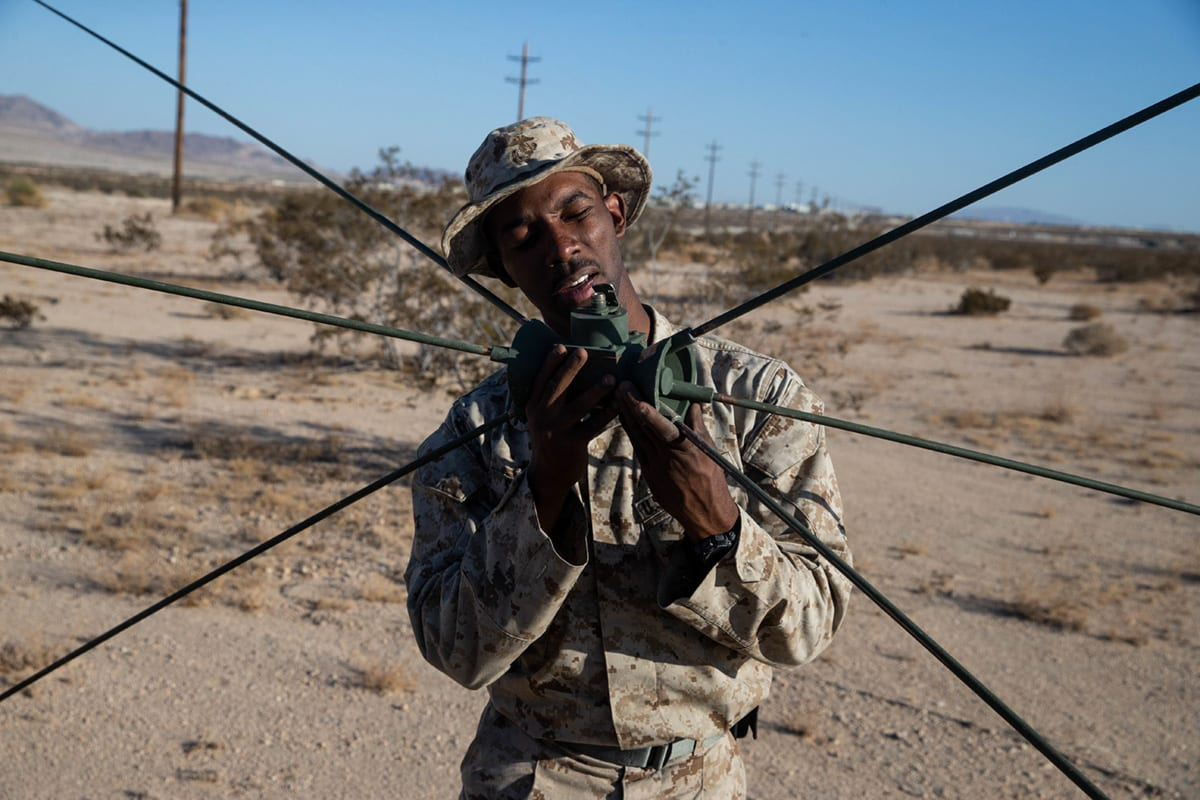 U.S. Marine Corps Cpl. David Storey, a field radio operator with Security Forces, Division Combat Skills Company (DCSC), Headquarters Battalion, Second Marine Division (2d MARDIV) examines an omnidirectional very-high-frequency antenna on Camp Wilson, Twentynine Palms, California, Oct. 14, 2019. (U.S. Marine Corps photo by Lance Cpl. Jesse Carter-Powell)