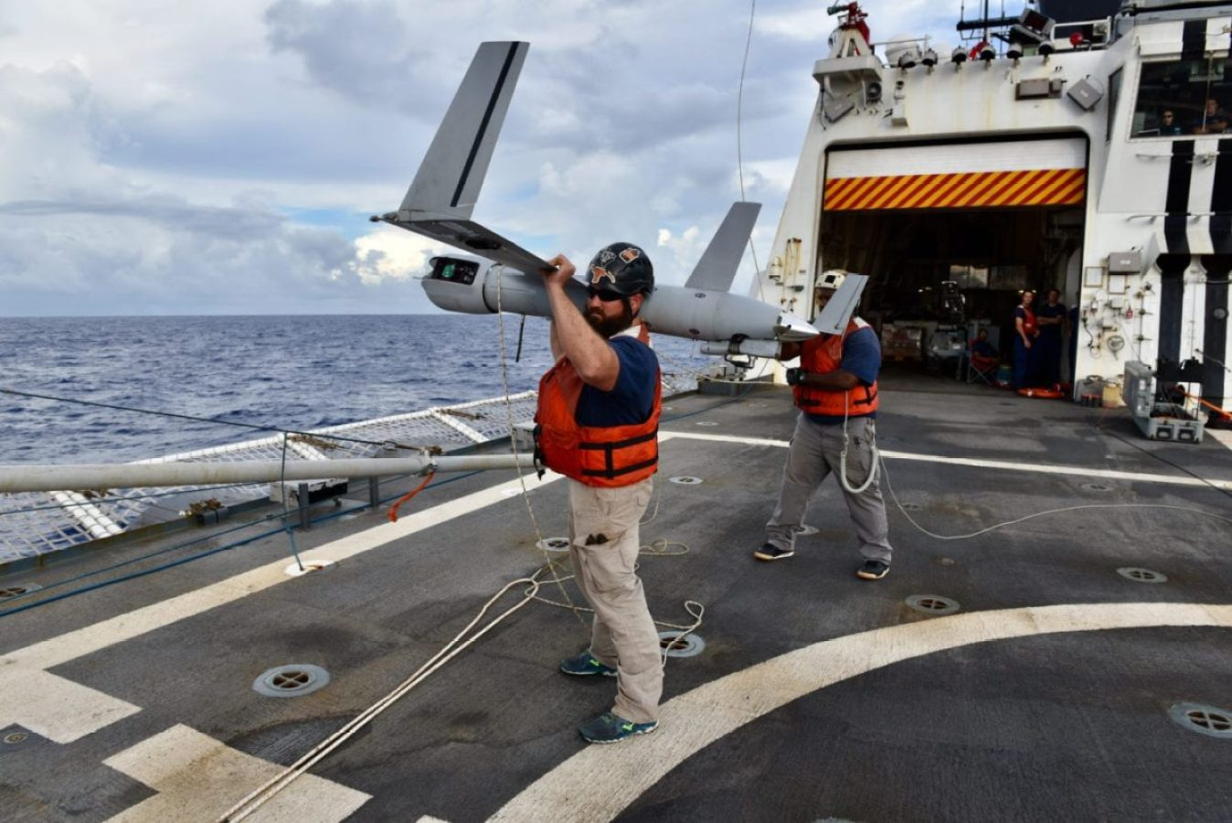 Mike McCord, Scan Eagle site lead, and Technician Dwight Smith, both of Dallas, recover a Small Unmanned Aerial System or drone aboard USCGC Stratton, in the Pacific, Oct. 31, 2019. The cutter's crew spent half of 2019 underway in support of joint operations in the Pacific. (U.S. Coast Guard photo by Chief Petty Officer Sara Muir/Released)