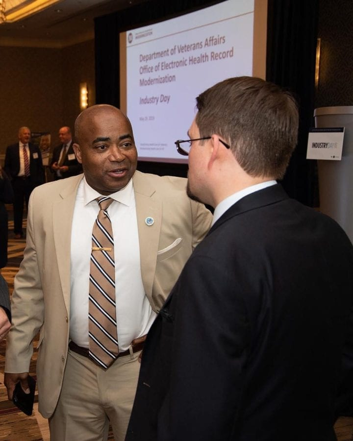 John H. Windom talks to an attendee during an industry day event May 29, 2019, at the Crystal Gateway Marriott in Arlington, Virginia. The industry day was an opportunity for the Office of Electronic Health Record Modernization to provide attendees with an update about VA's effort to replace its current electronic health record systems with the commercial-off-the-self solution - Cerner Millennium - now being deployed by the Department of Defence (DOD). The EHRM initiative will leverage an existing commercial solution to achieve interoperability within VA, with DOD, and with community care providers. A single interoperable solution across VA and DOD will facilitate the secure transfer of active-duty service members' health data as they transition to veteran status.