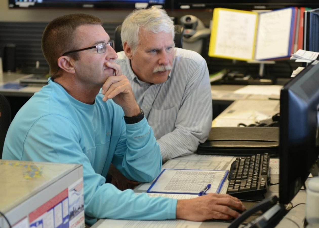 Robert Hutchinson and Kevin T. Coyne, civilian search and rescue coordinators at Sector St. Petersburg, Florida, create a search plan at the sector, Dec 17, 2014.