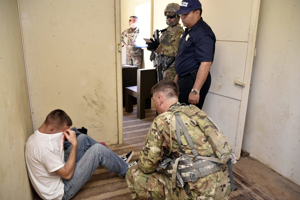 Soldiers visiting the chief of police during a psychological operations training scenario become concerned about the mistreatment of a prisoner in the adjacent cell. The PSYOP course at Fort Hunter Liggett, California trains Soldiers and Marines to build trust among the village leaders and to navigate cultural differences while trying to keep the peace among different factions. (Photo by Cynthia McIntyre)