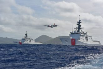 Coast Guard Cutter Midgett (WMSL 757), right, meets Coast Guard Cutter Kimball (WMSL 756) off Diamond Head Aug. 16, 2019 while a C-130 Hercules aircraft from Air Station Barbers Point flies between them.