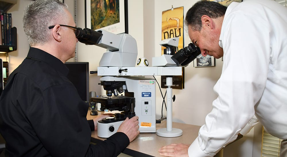 From left, JAHVH pathologists Dr. Andrew Borkowski and Dr. Stephen Mastorides examine tissue sample slides under a microscope. The microscope also captures images that can train the computers.