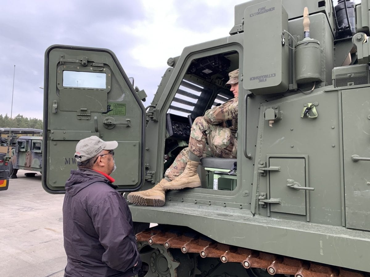 Paul Lopez, OFT trainer, checks in with a 1-6 FA Battalion 13M who is performing his Preventative Maintenance Check in the motor pool at the U.S. Army Base in Grafenwoehr, Germany. (Photo Credit: Kinsey Lindstrom)