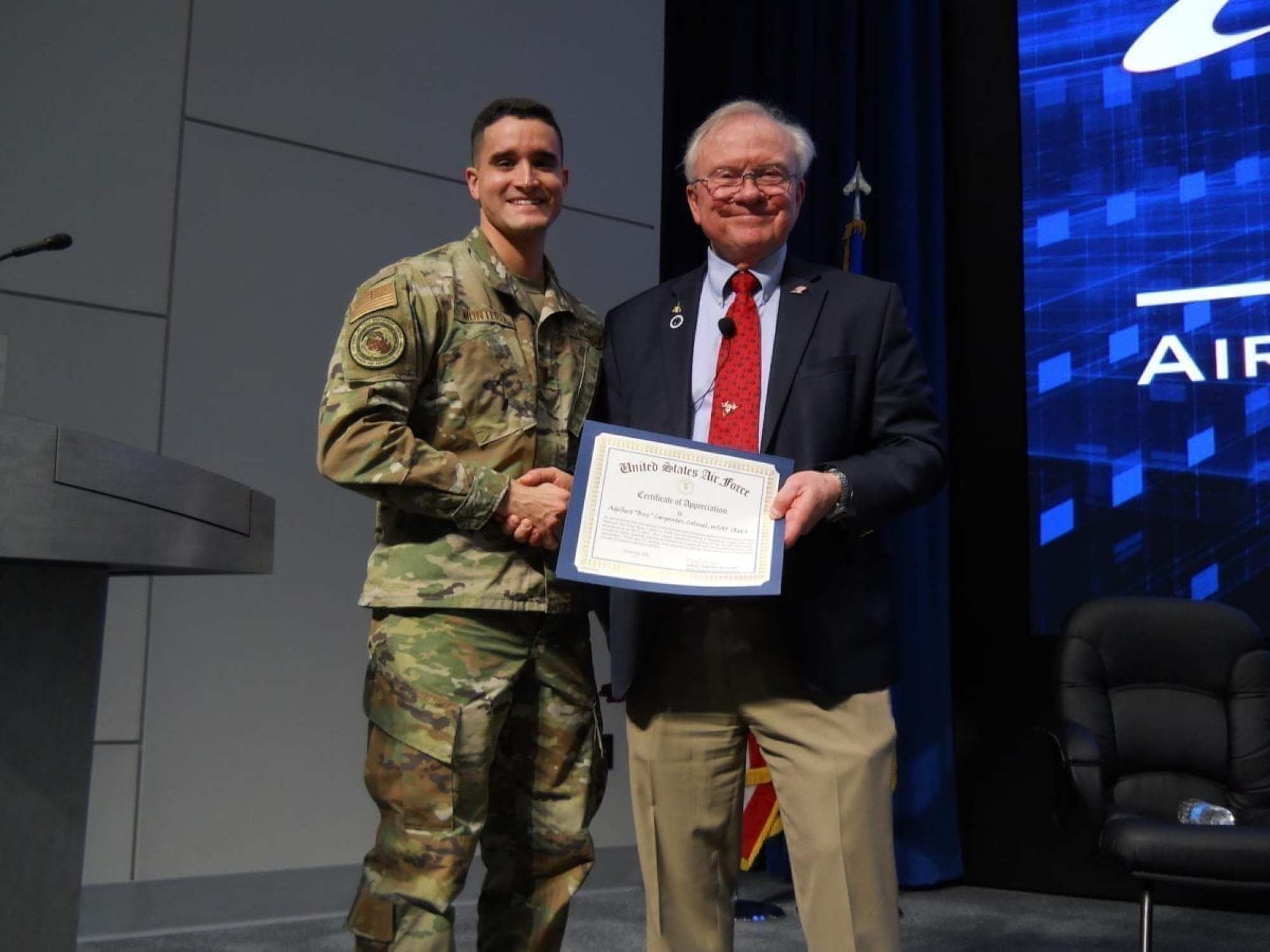 """Second Lt. Joseph Montero, AFLCMC Business and Enterprise Systems Directorate, presents a certificate of appreciation to Col. Adelbert """"Buz"""" Carpenter after his presentation on the SR-71. (courtesy photo)"""