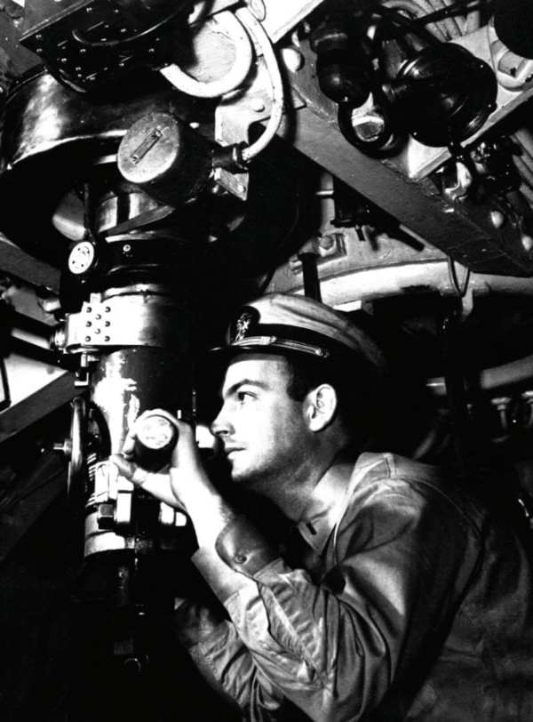 A submarine officer peers through the periscope of a U.S. Navy submarine during World War II.