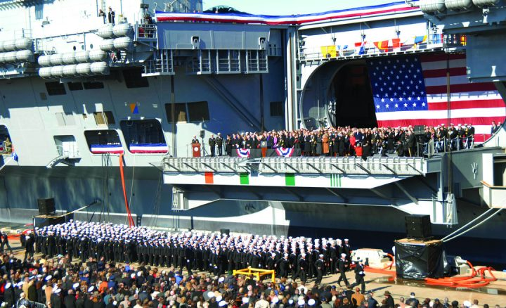 Audience members listen to remarks during the commissioning ceremony for the aircraft carrier USS George H.W. Bush (CVN 77) at Naval Station Norfolk, Virginia. Ship commissionings are among the most visible activities undertaken by the Navy League.
