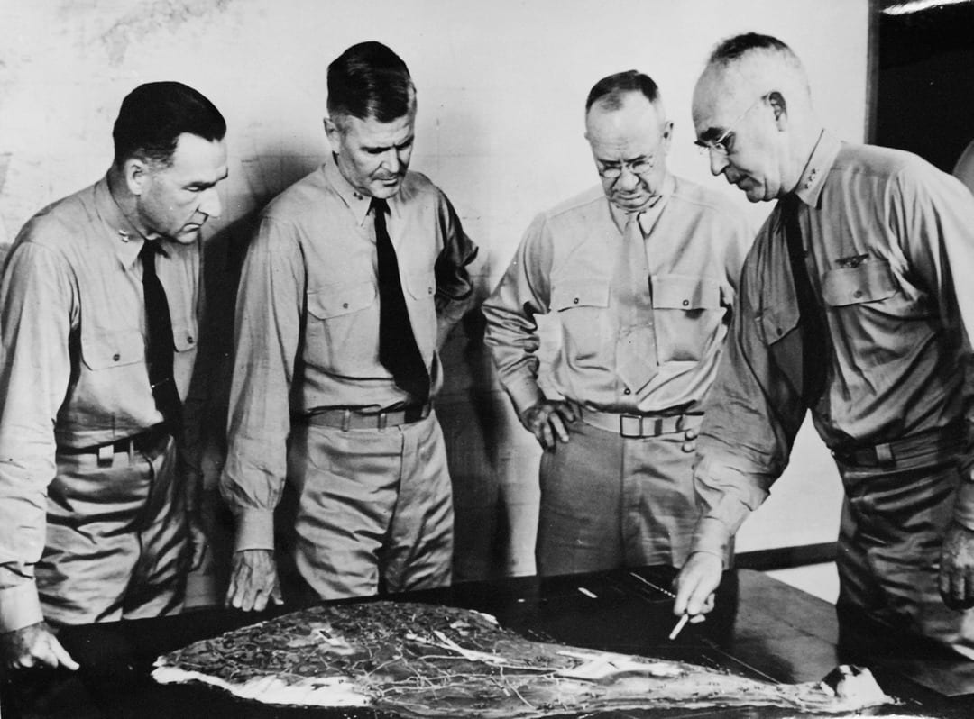 """Pictured from left to right, Capt. William H.P. Blandy, USN; Rear Adm. Harry W. Hill, USN; Lt. Gen. Holland M. """"Howlin' Mad"""" Smith, commander of U.S. Marines on the island; and Vice Adm. Richmond K. Turner, commander in chief of U.S. operations on Iwo Jima, examine a scale model of Iwo Jima as they discuss plans for attacking the heavily defended island fortress. U.S. NAVY PHOTO"""